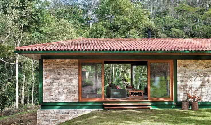 Fachada de casa de campocom pintura verde e detalhe em pedra