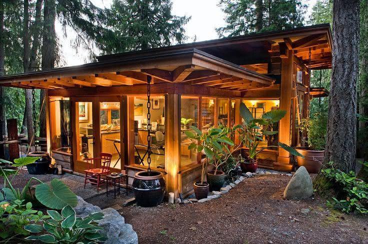 Fachada de casa de campo feita com madeira e portas de vidro.
