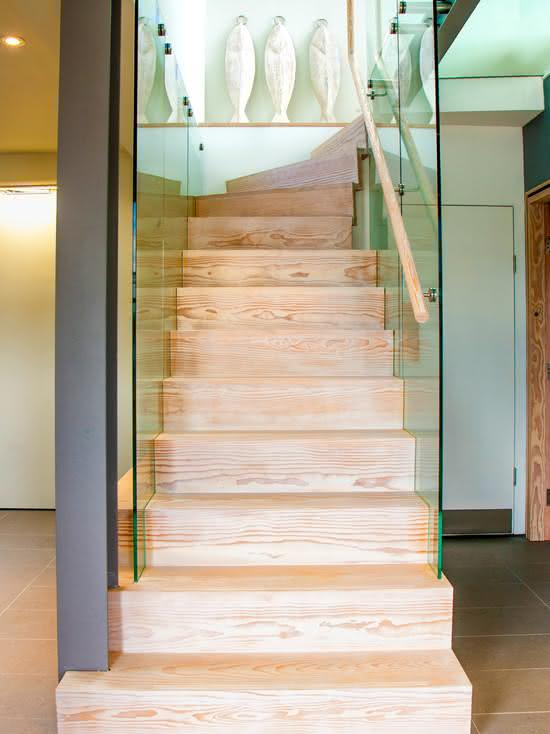 Escada de madeira com painel de vidro fixado no degrau