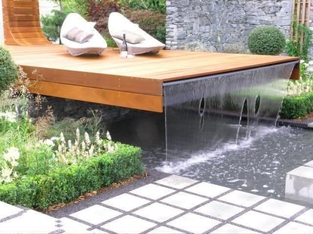 Cascata para piscina saindo do deck em madeira
