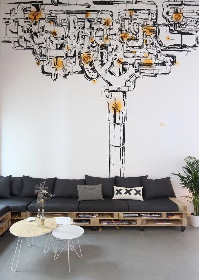 Sofá de pallet e grafite na parede da sala