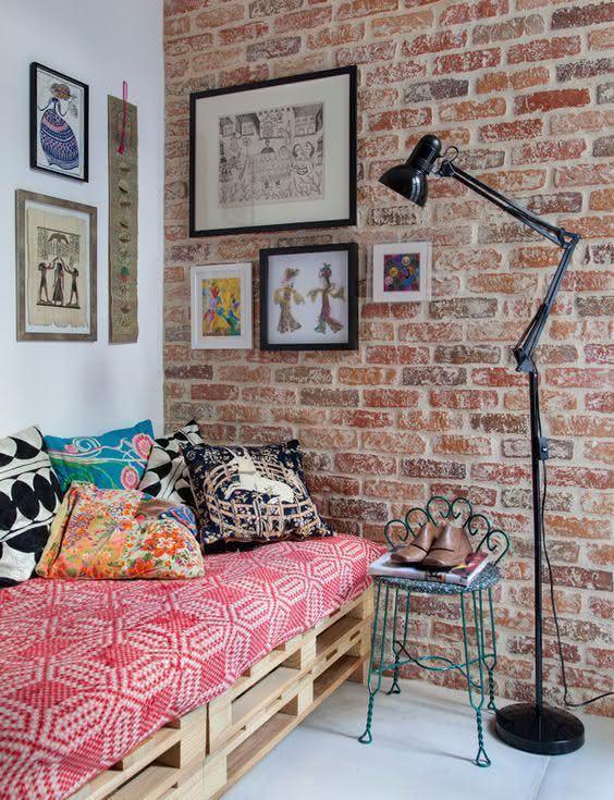 Sala com parede de tijolos e sofá de pallet