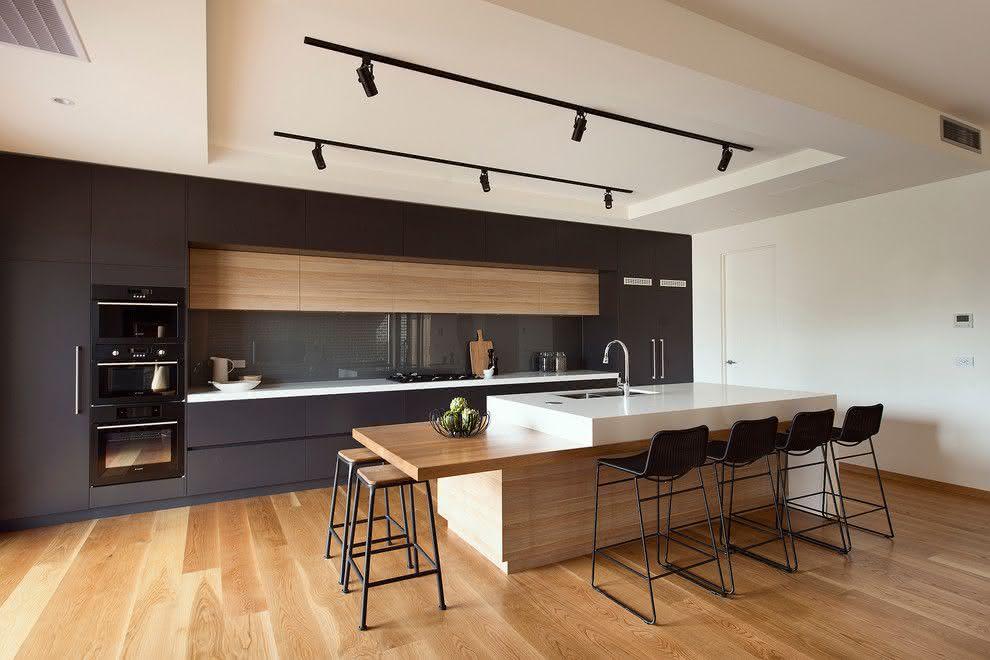 Cozinha ampla que combina o preto, o branco e os tons claros da madeira