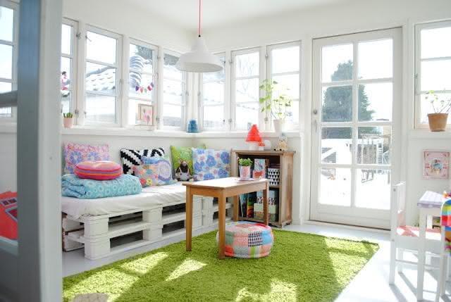 Sofá de pallet pintado de branco com almofadas coloridas