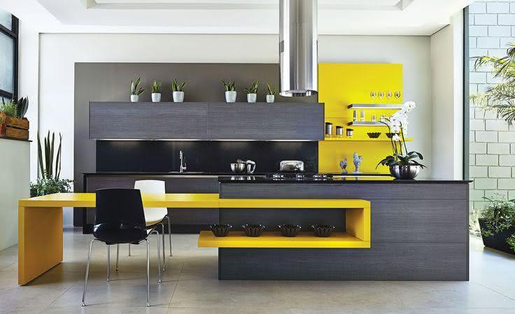 Projeto de cozinha com ilha central preta e mesa embutida em madeira laqueada amarela