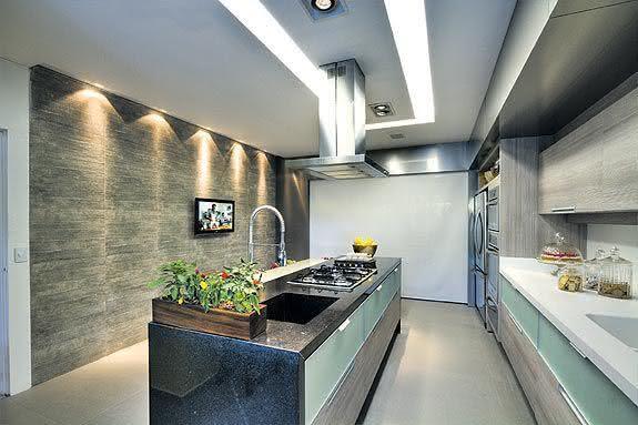 Cozinha com ilha central com gaveteiros em madeira e bancada revestida em pedra preta