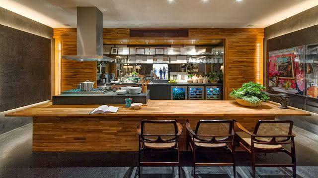 Proposta de cozinha com ilha central de madeira ampla com cadeiras