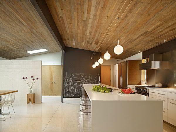 Cozinha com ilha central Branca com bancada para preparar alimentos e banquetas em acrílico transparente