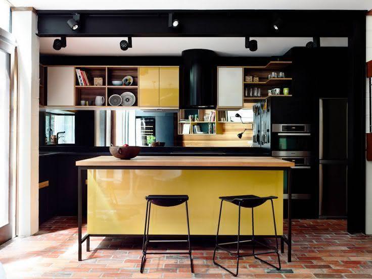 Cozinha com ilha central com estrutura metálica preta, tampo em madeira e base laqueada amarela