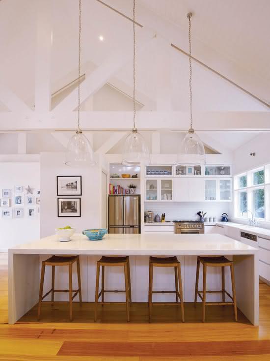 Cozinha com ilha central e espaço inferior para as banquetas