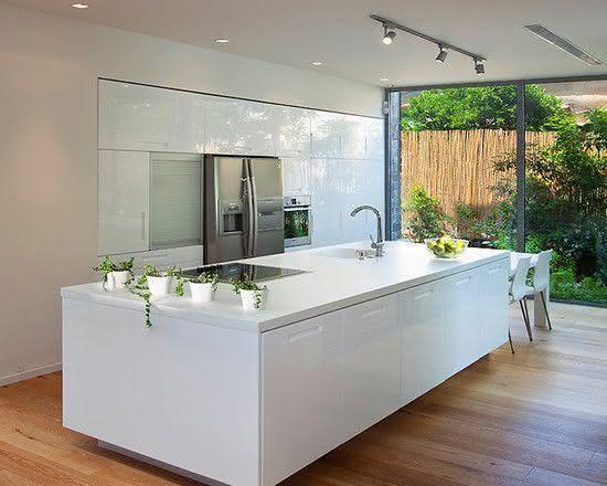Proposta de cozinha com ilha central laqueada branca com mesa para refeição