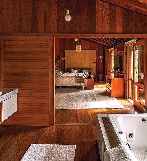 decoracao de interiores em casas de madeira: Casa de fazenda com parede de quarto de solteiro revestido em madeira