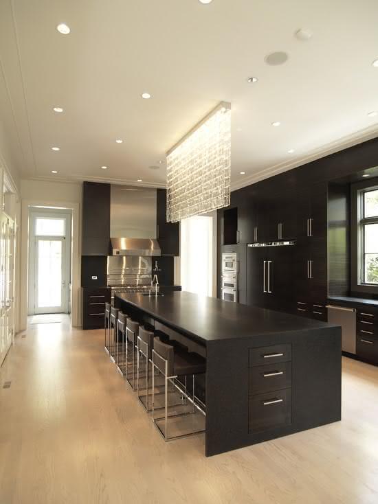 Cozinha com ilha central preta com espaço para seis banquetas e luminária de cristal pendente sobre a bancada