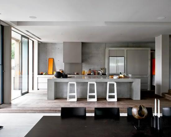 Cozinha com ilha central em cimento com banquetas brancas