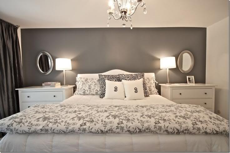 Foto tirada de frente de cama de casal com decoração leve e amena. Parede do fundo pintada de cinza claro, contrastando com paredes das laterais, móveis e objetos de decoração brancos.