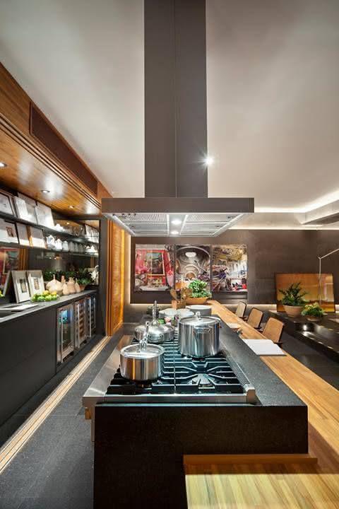 Cozinha com ilha central e mesa de jantar extensa