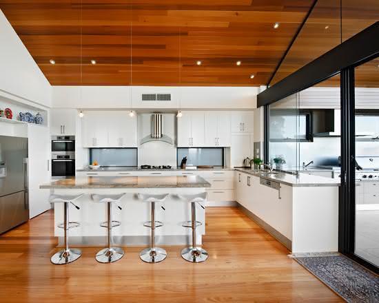 Cozinha com ilha onde há uma bancada para refeição sem cooktop