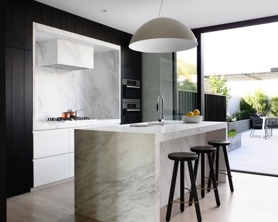 Cozinha com ilha central em pedra branca