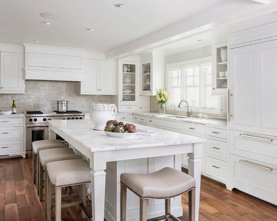 Cozinha com ilha central com decoração em cores neutras