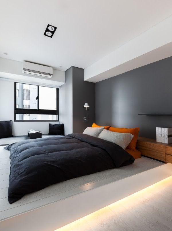 Quarto de casal com cama baixa e parede cinza