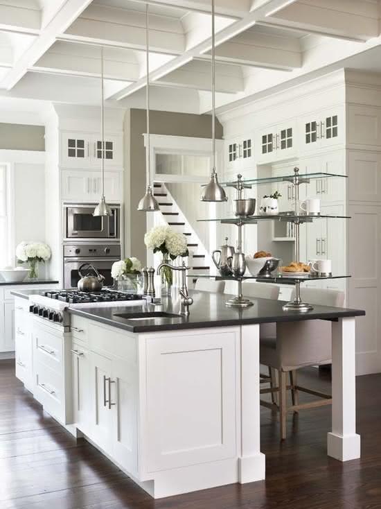 Cozinha com ilha central com pia, fogão e pendentes pequenos sobre a bancada
