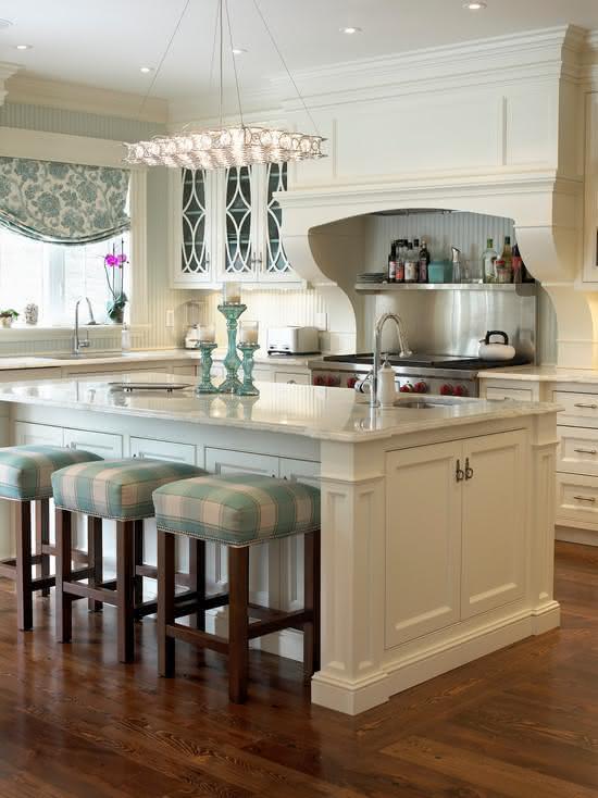 Cozinha com ilha central com armários embaixo da bancada