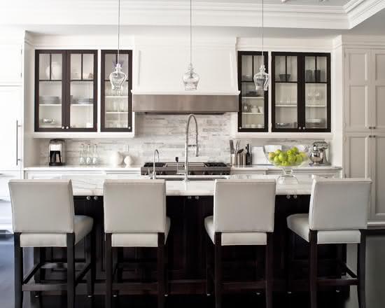 Cozinha com ilha central onde há uma bancada em mármore com banquetas estofadas