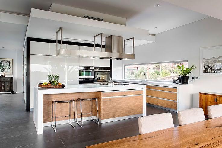 Cozinha com ilha central em madeira na cor natural e branca com banquetas