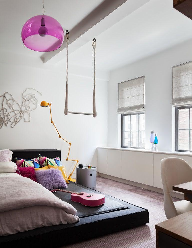 Decoração de quarto clean com detalhes na cor rosa e almofadas coloridas