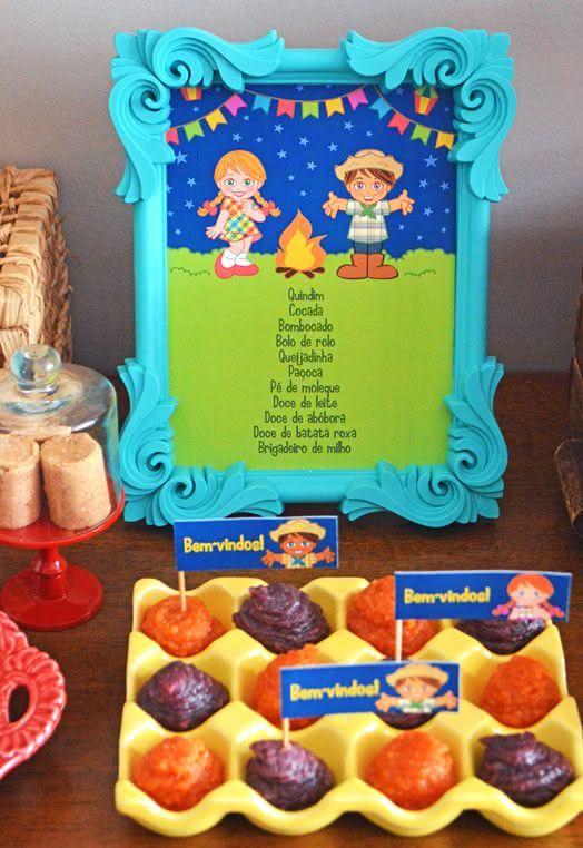 Mesa de doces com menu da festa junina