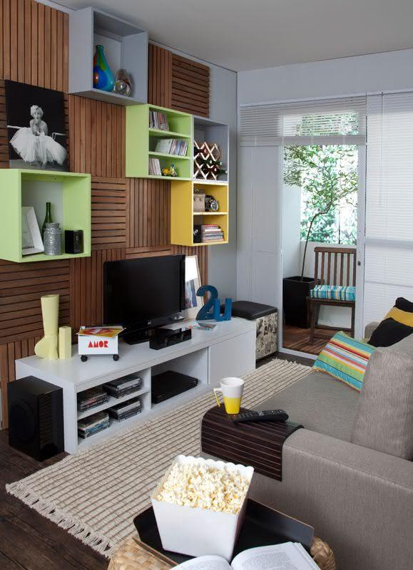 Sala De Tv Pequena Ideias ~ Imagem 37 – Sala de TV com painel de madeira e nichos coloridos na
