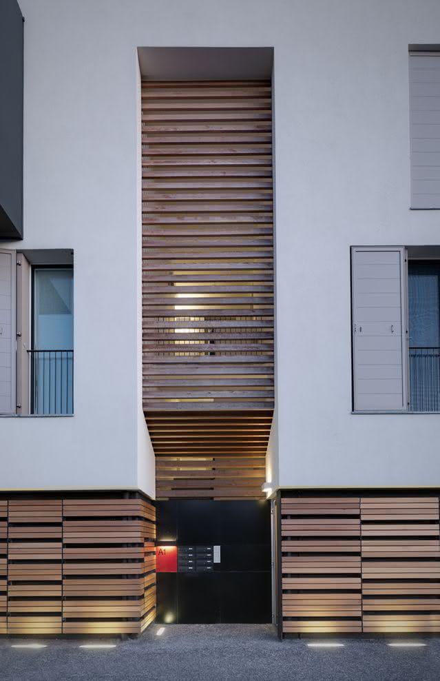 Os detalhes em madeira da fachada reaparecem nos portões de acesso a garagem
