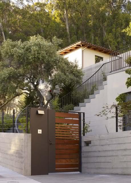 A mistura do metal e a madeira no portão ficou perfeita para esse modelo de casa.