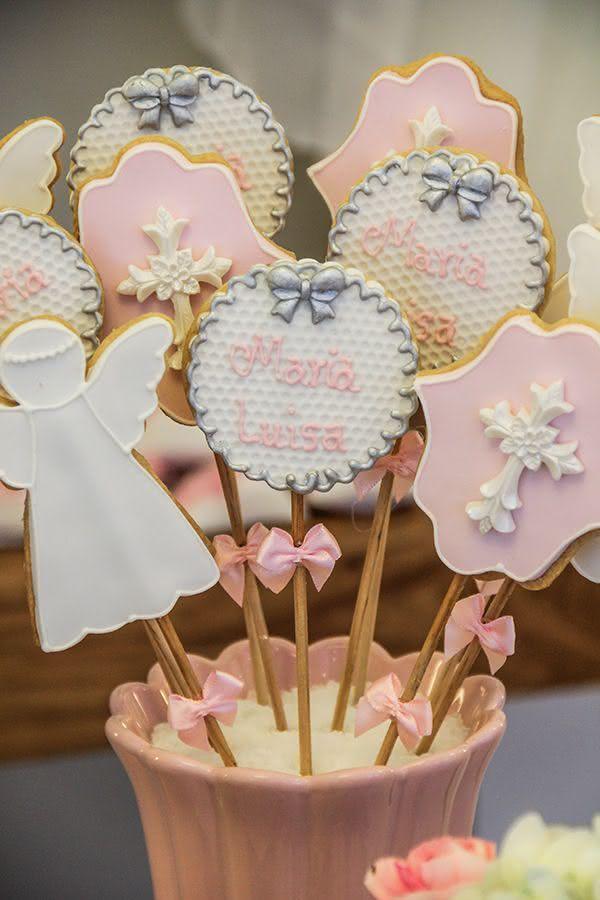 Aproveite a altura dos pirulitos de biscoitos e posicione-os na área principal. Aqui, eles seguem com as cores rosa e branco.