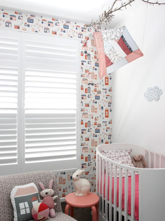 Quarto de bebê com papel de parede e estampa de casinhas