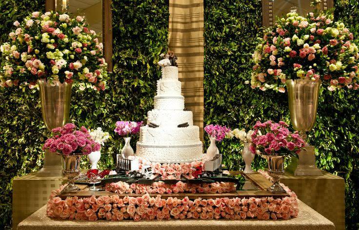 Imagem 30 – Mesa de bolo para casamento com decoração de rosas
