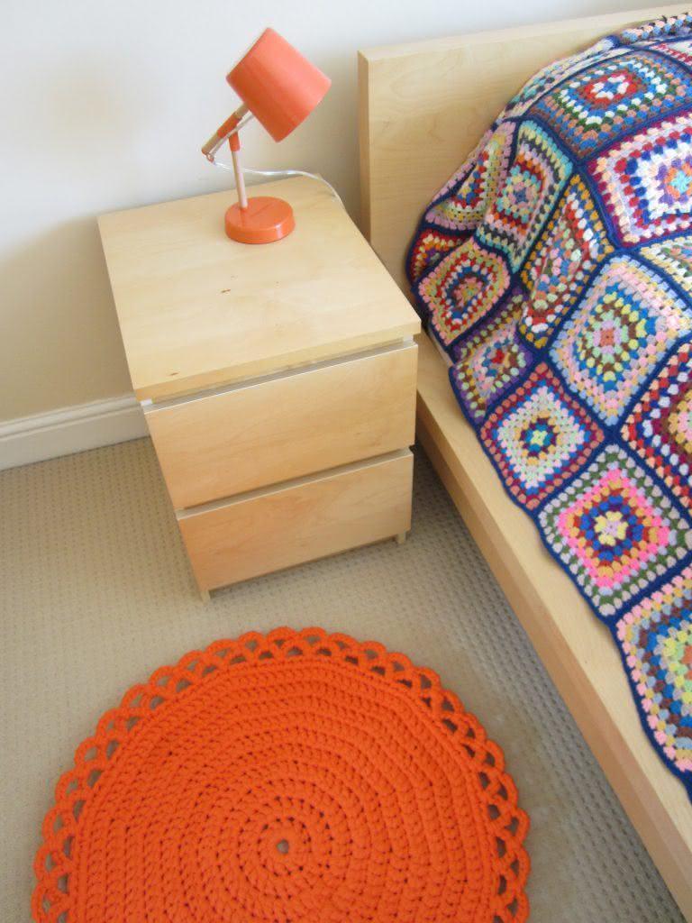 Tapete de crochê redondo ao lado da cama