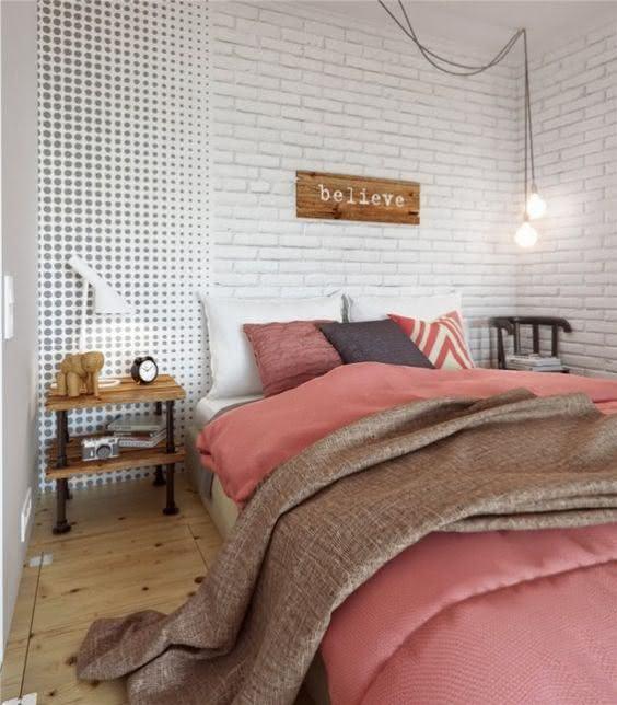 Quarto de casal com papel de parede que imita o tijolinho