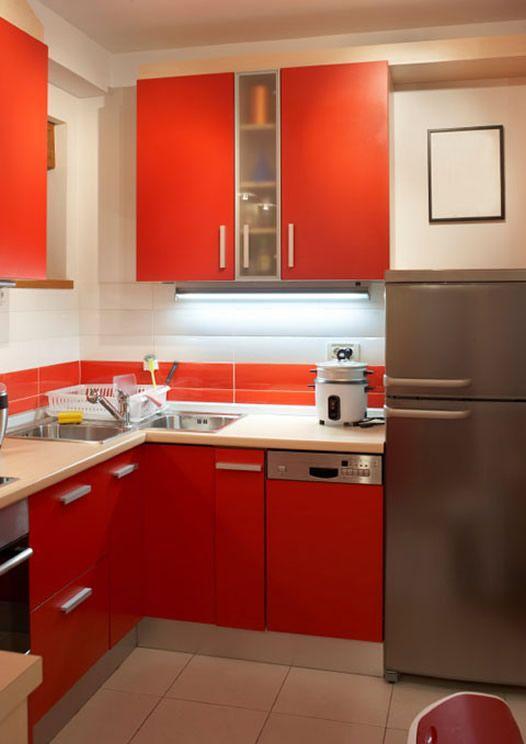 Armário de cozinha vermelha e equipamentos em inox fazem a combinação perfeita