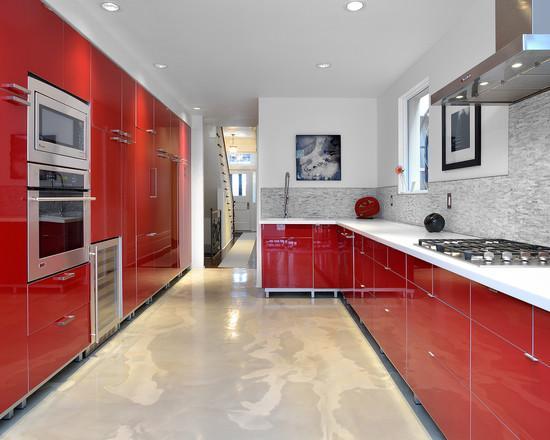 A cozinha vermelha combina muito bem com o piso em cimento queimado