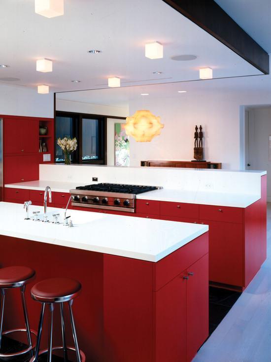 Modelo de cozinha ideal com bancada central e decoração vermelha