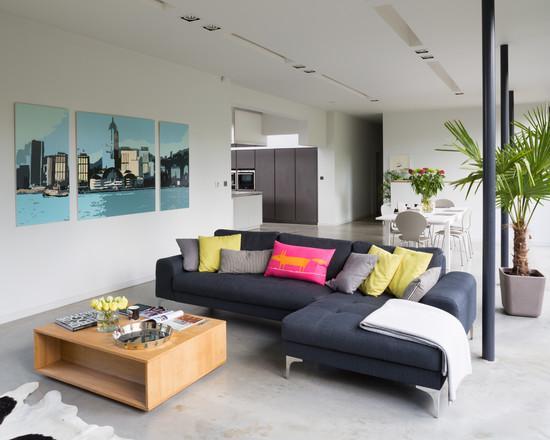 Os sofás pretos com o piso em cimento queimado fazem uma dupla perfeita