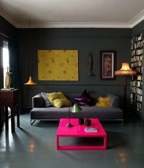 Sala com paredes escuras e objetos com cores vibrantes