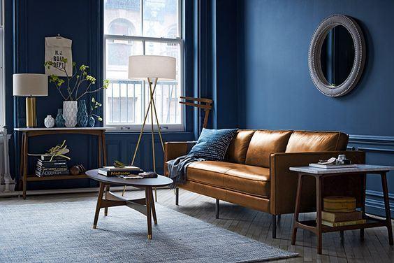 O caramelo do sofá e os tons de madeira dos móveis tem um interessante efeito sobre o azul das paredes