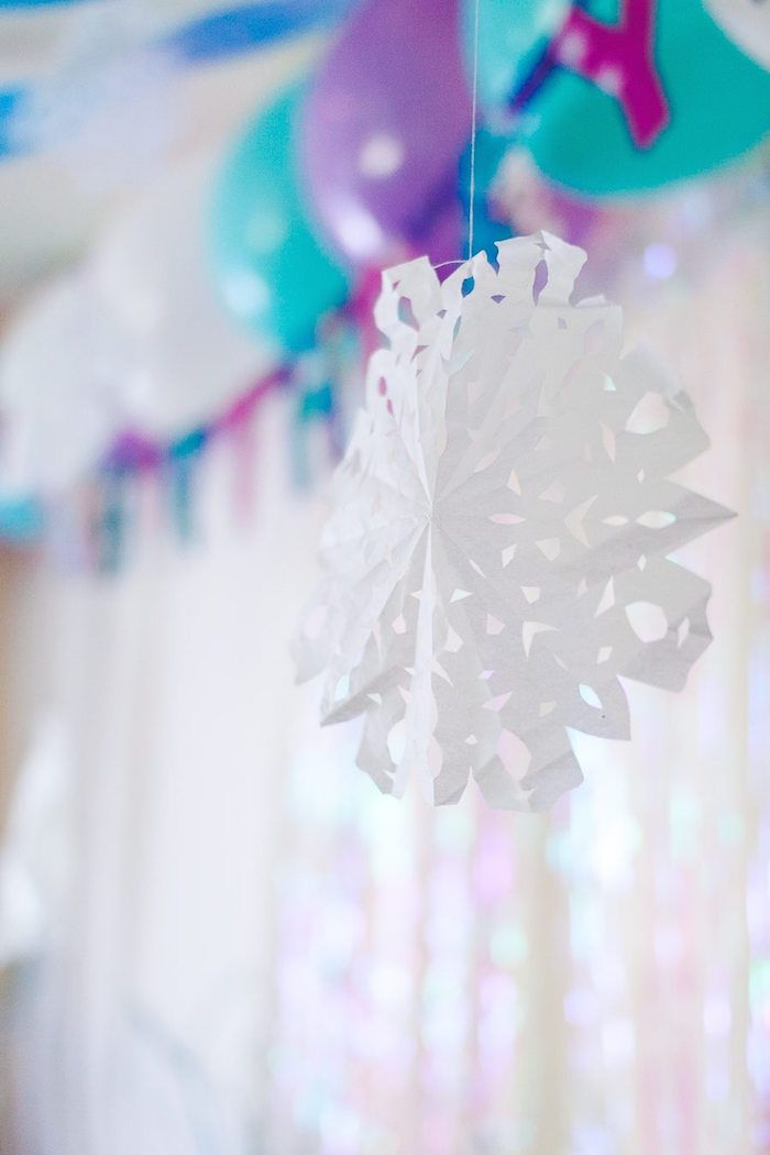 Decore o ambiente com flocos de neve de papel.