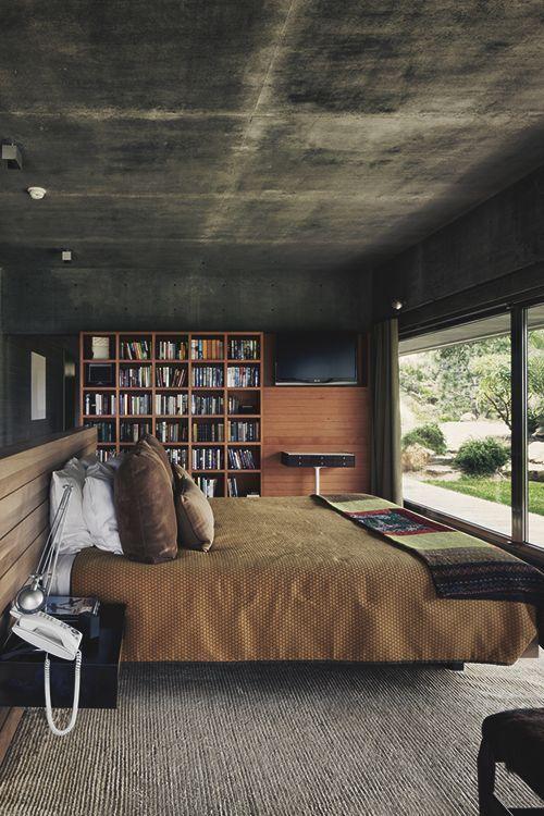 O quarto de casal vem com materiais como o concreto e a madeira