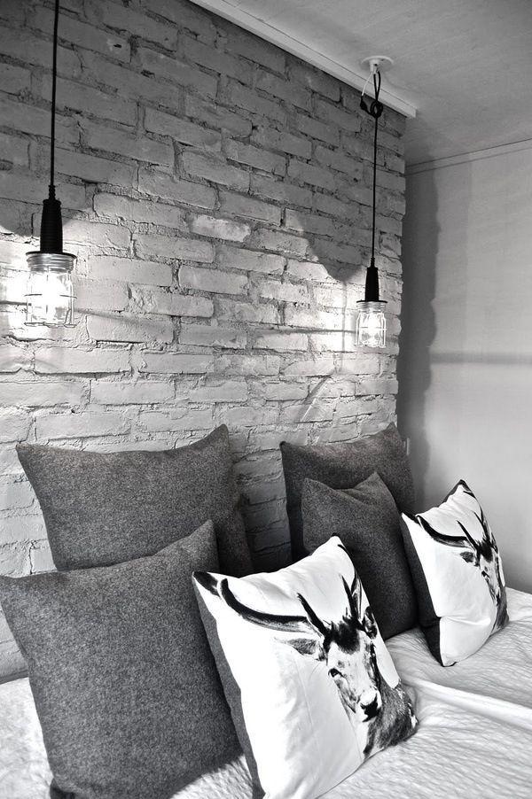 Parede de tijolos com luminárias pendentes combinam com as laterais da cama