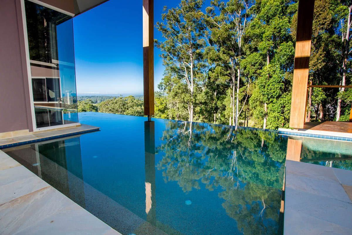 O fechamento de vidro da casa permite uma conexão com a piscina e a paisagem