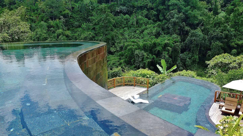 O verde da piscina entra em harmonia com a vegetação ao fundo, fazendo uma junção com a natureza