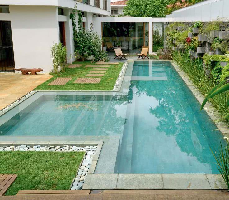 Pedrinhas e arbustos acrescentam ao paisagismo da área da piscina